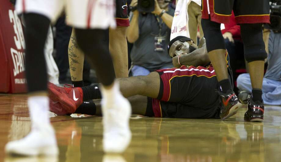 LeBron James of the Heat lies on the floor after colliding with Rockets center Dwight Howard. Photo: Brett Coomer, Houston Chronicle