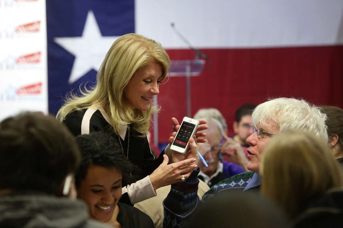 Volunteer Daniel O'Leary hands Senator Wendy Davis his phone so she can talk to a voter he called as she calls voters and thanks volunteers working at the phone bank at her campaign headquarters in Fort Worth on Tuesday, March 4, 2014.