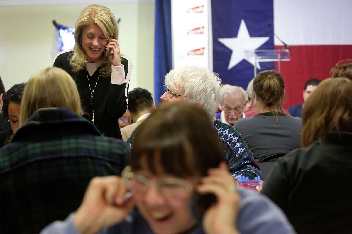 Senator Wendy Davis talks to a voter who volunteer Daniel O'Leary, right, called as she calls voters and thanks volunteers working at the phone bank at her campaign headquarters in Fort Worth on Tuesday, March 4, 2014.