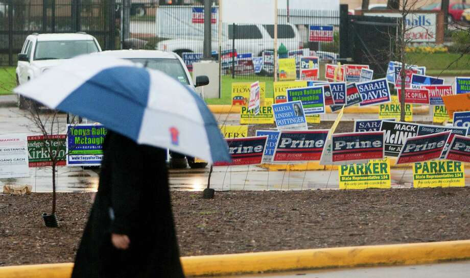 Rain and campaign signs cover the ground outside the Houston Metropolitan Multi-Services Center as the doors open to voters on Tuesday. Photo: Cody Duty, Staff / © 2014 Houston Chronicle