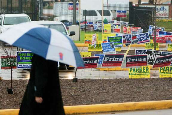 Rain and campaign signs cover the ground outside the Houston Metropolitan Multi-Services Center as the doors open to voters on Tuesday.