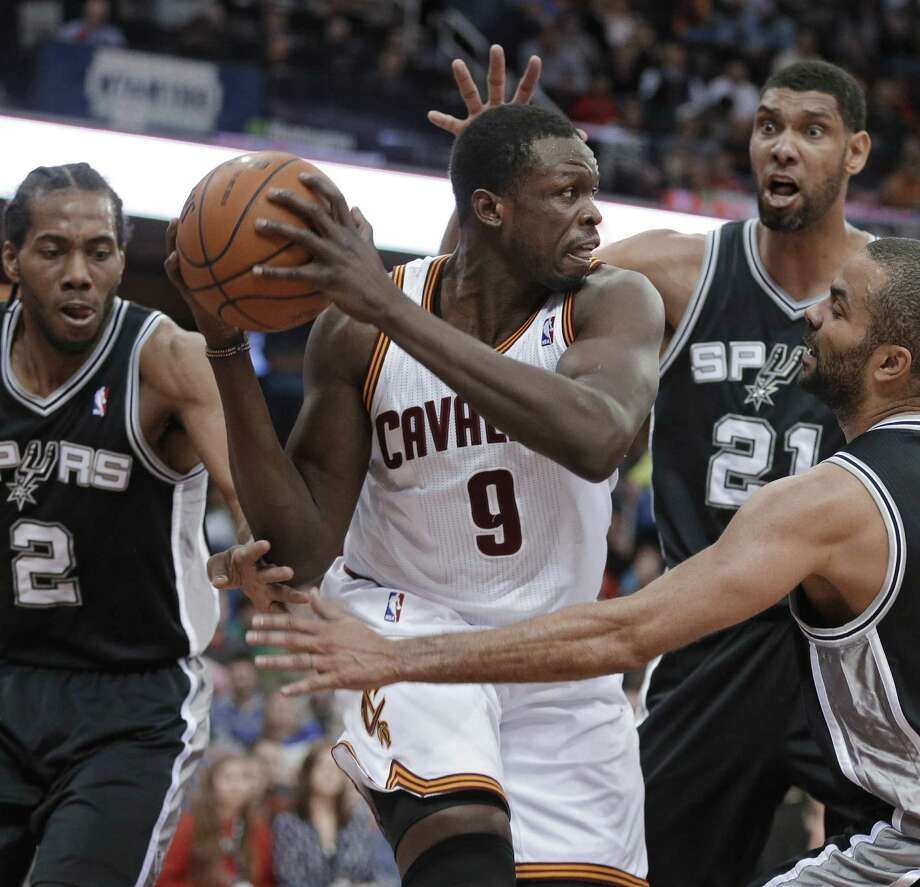 Cavaliers forward Luol Deng is surrounded by Kawhi Leonard (2), Tim Duncan (21) and Tony Parker during the third quarter of the Spurs' 122-101 victory Tuesday in Cleveland. Photo: Mark Duncan, Associated Press / AP
