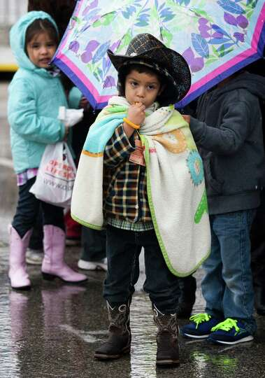 Bayron Garza, 5, bundles up under a blanket as he walks through the carnival section of Rodeo Housto