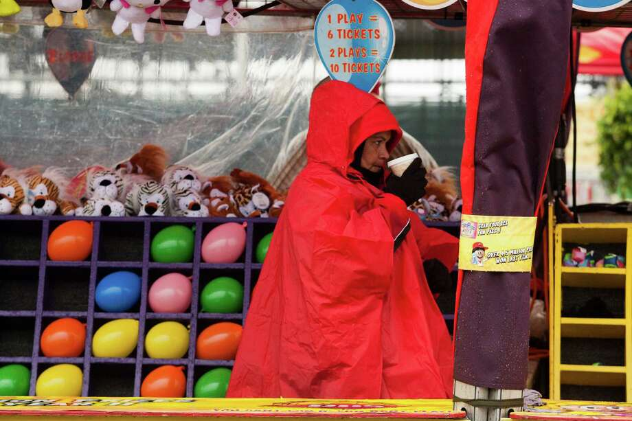 A carnival worker attempts to stay warm on a chilly wet day at Rodeo Houston on Tuesday, March 4, 2014, in Houston. Photo: J. Patric Schneider, For The Chronicle / © 2014 Houston Chronicle