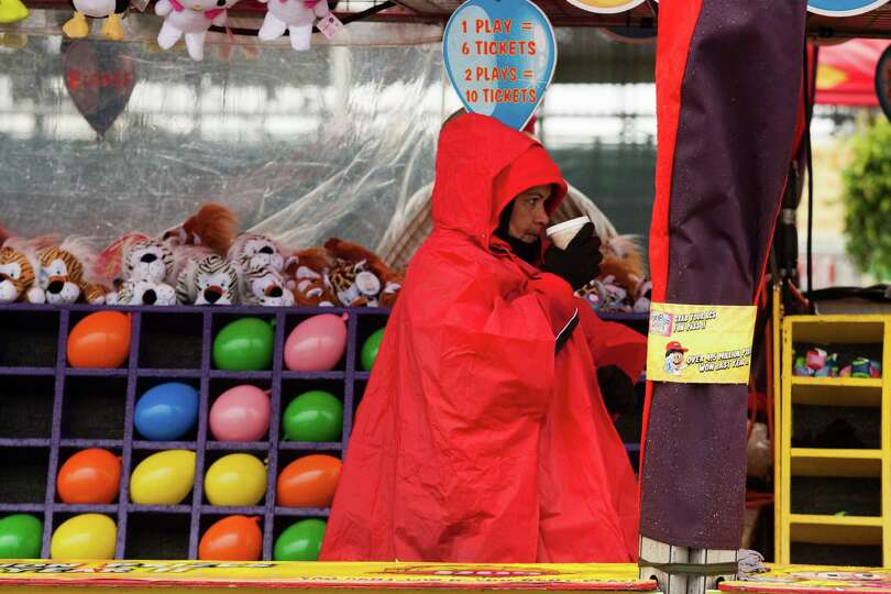 A carnival worker attempts to stay warm on a chilly wet day at Rodeo Houston on Tuesday, March 4, 20
