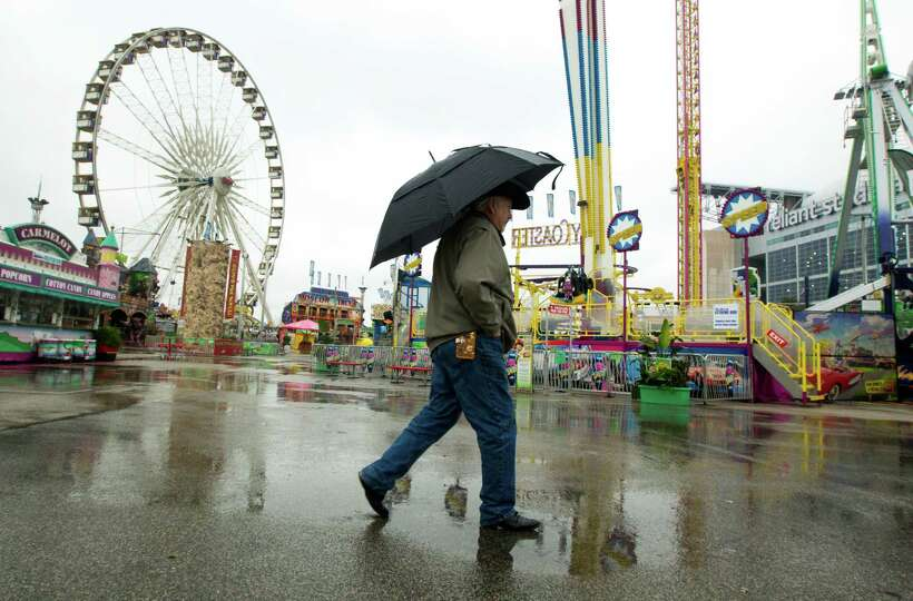 A man walks through the soggy grounds of the carnival at Rodeo Houston on Tuesday, March 4, 2014, in