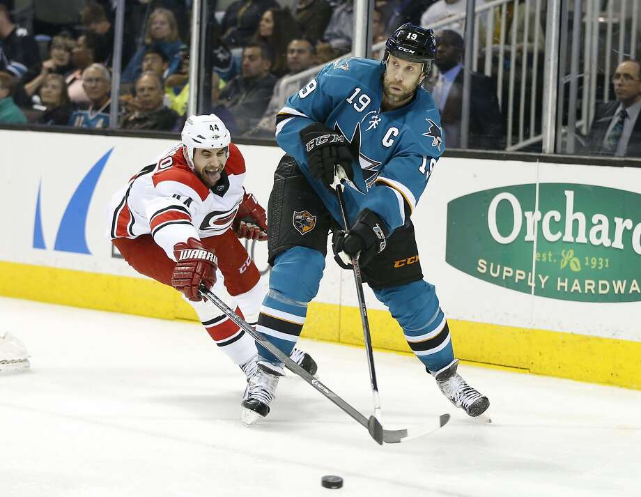 Sharks center Joe Thornton (19) moves around Hurricanes defenseman Jay Harrison, who scored the winning goal. Photo: Robert Stanton, Reuters