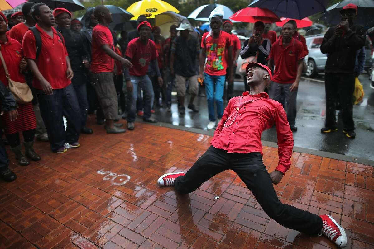 PRETORIA, SOUTH AFRICA - MARCH 04: Supporters of the Economic Freedom Fighters (EFF) rally and sing songs outside Pretoria High Court on March 4, 2014 in Pretoria, South Africa. The EFF are saying that the R600,000 deposit required when submitting candidates names for the upcoming national elections are unjust and are seeking an interdict in court against it. (Photo by Christopher Furlong/Getty Images) *** BESTPIX ***