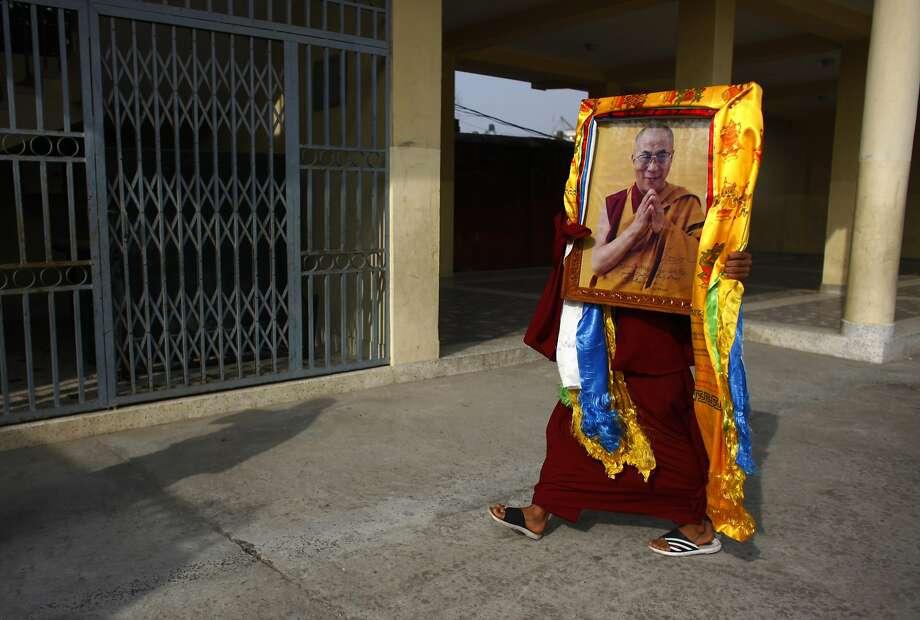 A monk (top) carries a portrait of the Dalai Lama. Photo: Niranjan Shrestha, Associated Press