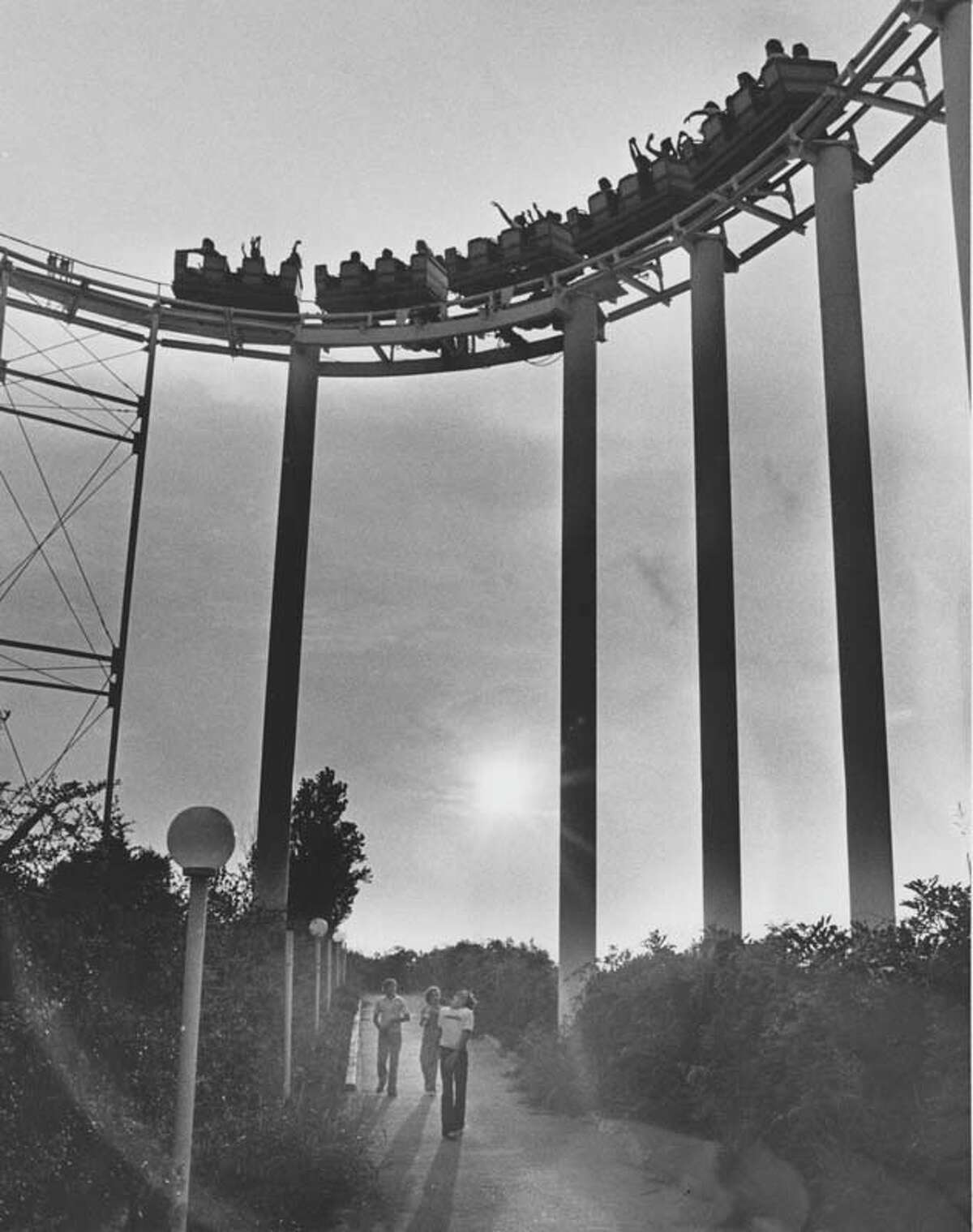 Passersby walk underneath AstroWorld's first major roller coaster, the Dexter Freebish Electric Roller Ride.