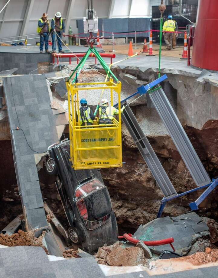 Workers remove three damaged Corvettes from the sinkhole beneath the National Corvette Museum in Bowling Green. Photo: Newspress USA