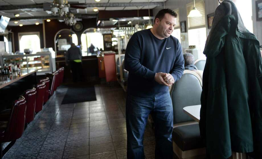 Second-generation owner Leo Koutikas talks to a customer during lunch Tuesday, Mar. 4, 2014, at New Colony Diner in Bridgeport, Conn. Photo: Autumn Driscoll / Connecticut Post
