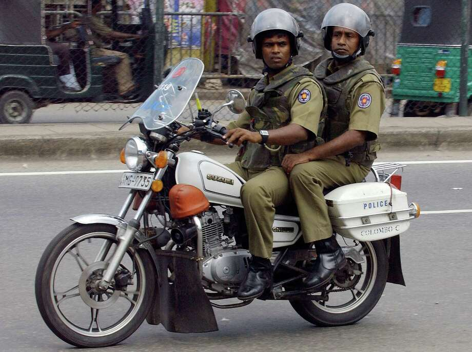 A couple of Sri Lankan cops ride two-up on a tiny Suzuki GN125N. Photo: SANKA VIDANAGAMA, AFP/Getty Images / 2007 AFP