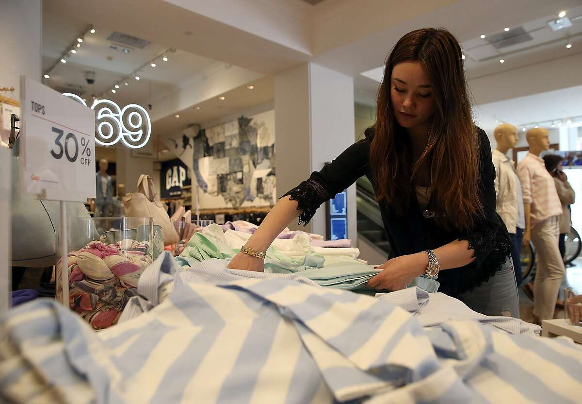 SAN FRANCISCO, CA - FEBRUARY 20: Gap employee Shinju Nozawa-Auclair folds clothes at a Gap store on February 20, 2014 in San Francisco, California. Gap Inc. announced that they will raise their minimum wage for U.S. employees to nine dollars in June of 2014 and to $10 by June of 2015. (Photo by Justin Sullivan/Getty Images)