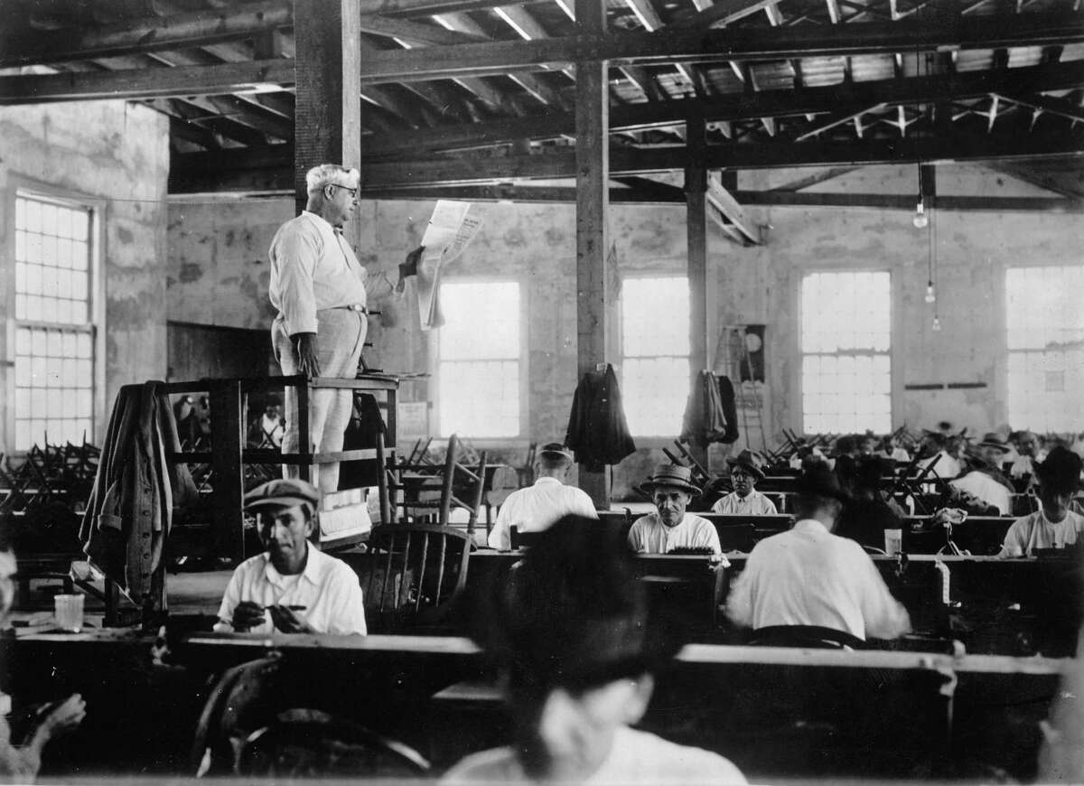 American factories sometimes employed guys like this, who stood or sat on elevated platforms and read books, newspapers and the like to the workers. Here, a newspaper reader entertains cigar rollers in Key West, Florida in 1930.