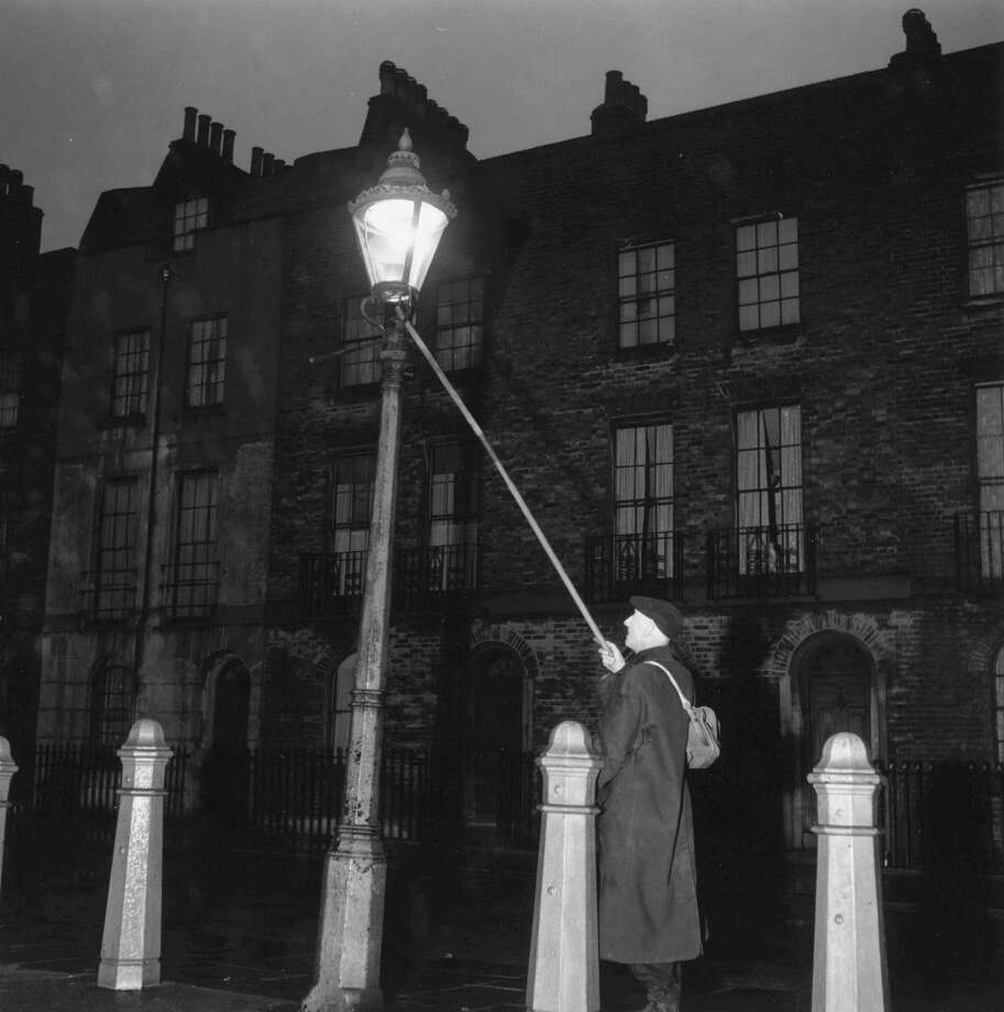 Our lives are a little less romantic since the lamplighter was made obsolete. London's oldest lamplighter, John Jennings, was lighting and extinguishing street lamps until the 1950s. Photo: Chris Ware, Getty Images / Hulton Archive