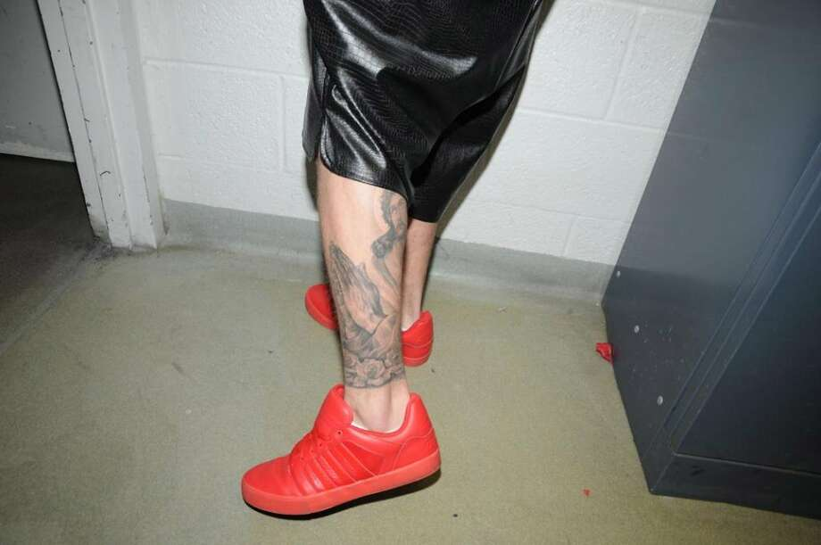 In this handout photo provided by the Miami Beach Police Department and released on March 4, 2014, singer Justin Bieber displays his tattoos for police documentation while in custody on January 23, 2014 in Miami Beach, Florida. Justin Bieber was arrested for driving under the influence, resisting arrest and driving without a valid driver's license. Photo: Handout, Getty Images