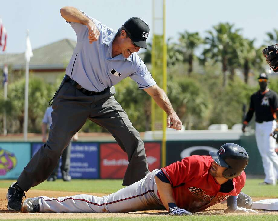 Angel in the infield:Third base umpire Angel Hernandez punches out the Twins' Brian Dozier after   Dozier overslid third base during a spring training game in Jupiter, Fla. Photo: Jeff Roberson, Associated Press