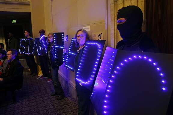 "Opponents of the Domain Awareness Center hold lighted boards spelling out, ""Sink the DAC,"" at a council meeting in Oakland, Calif., on Tuesday, March 4, 2014."