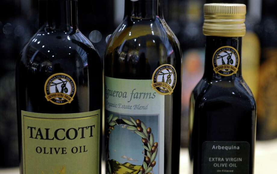 "This photo taken Feb. 14, 2014 shows dertification stickers are affixed to bottles of California olive oil displayed and for sale at the All Things Olive shop in Washington. It's a pressing matter for the tiny U.S olive oil industry. Shoppers are more often pouring European oil _ it's cheaper and viewed as more authentic than the American competition. And that's pitting U.S. producers against importers of the European oil. Some liken the battle to the California wine industry's struggles to gain acceptance decades ago. The tiny California olive industry says European olive oil filling U.S. shelves often is mislabeled and lower grade. They're pushing the federal government to give more scrutiny to imported varieties. One congressman-farmer even goes as far as suggesting labels on imported oil say ""extra rancid"" rather than extra virgin. Stricter standards might help American producers grab more market share from the dominant Europeans.  (AP Photo/Susan Walsh) ORG XMIT: WX203 ORG XMIT: MER2014021812305506 Photo: Susan Walsh / AP"