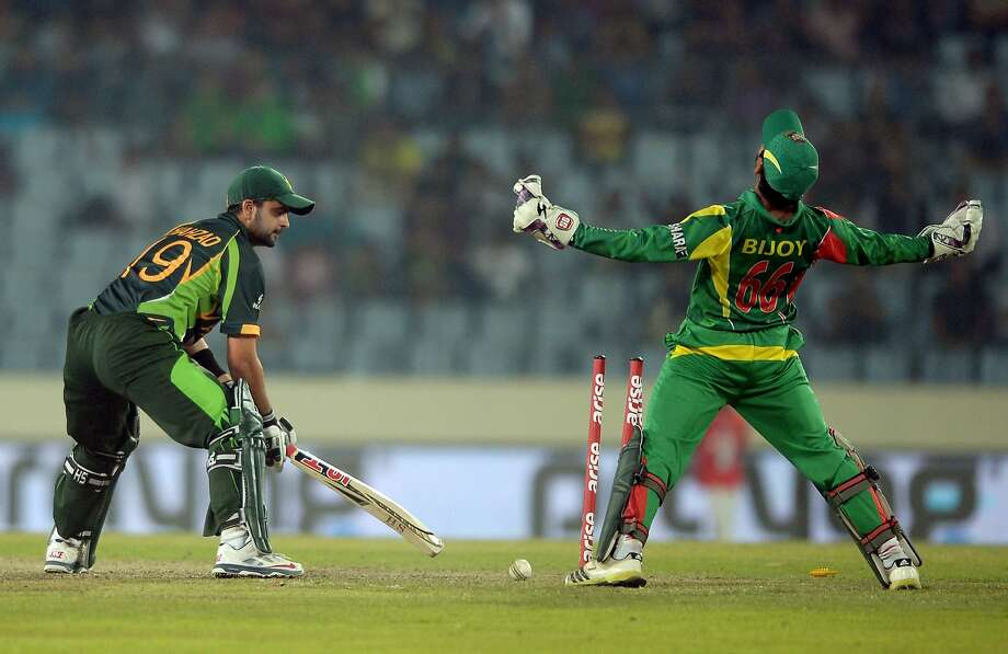 """I'm the king of the world!At the Asia Cup cricket tournament, Bangladeshi wicketkeeper Anamul Haque (right) """"celebrates the   wicket of Pakistani batsman Ahmed Shehzad."""" We have no idea what   that means, but it's obviously thrilling Hague. Photo: Dibyangshu Sarkar, AFP/Getty Images"""