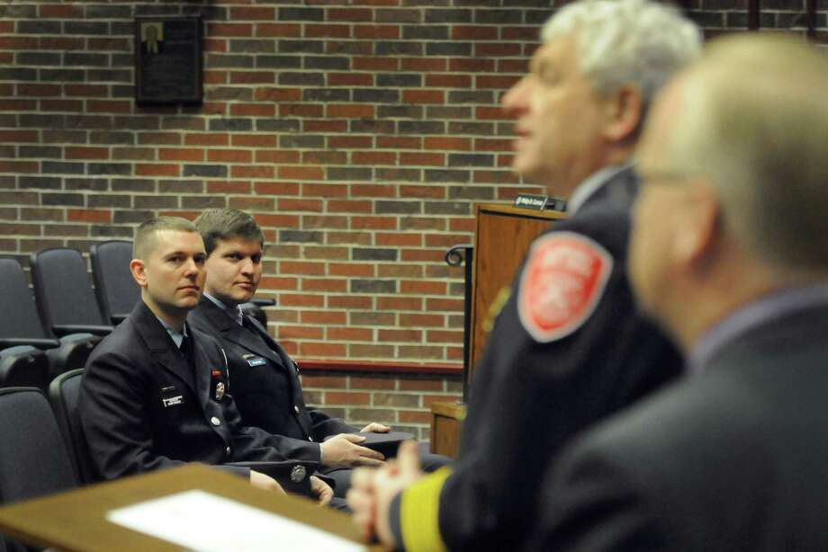 Gary Bruce, 34, left, and Shey Hanson, 35, listen to Chief Geoff Herald speak at a promotion ceremony for the two Danbury firefighters at City Hall Wednesday, March 5, 2014. Gary Bruce was promoted to Deputy Fire Marshal. Shey Hanson was promoted to the rank of lieutenant. Photo: Carol Kaliff / The News-Times