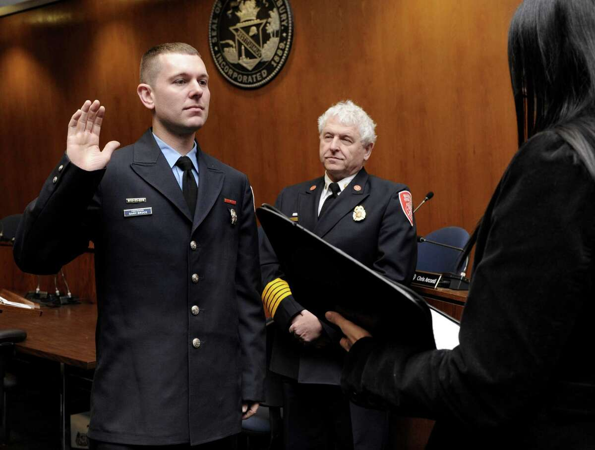 Gary Bruce, 34, left, is sworn in as Deputy Fire Marshal by Town Clerk Lori Kaback at a promotion at Danbury City Hall Wednesday, March 5, 2014, in Danbury, Conn. Fire Chief Geoff Herald is center.