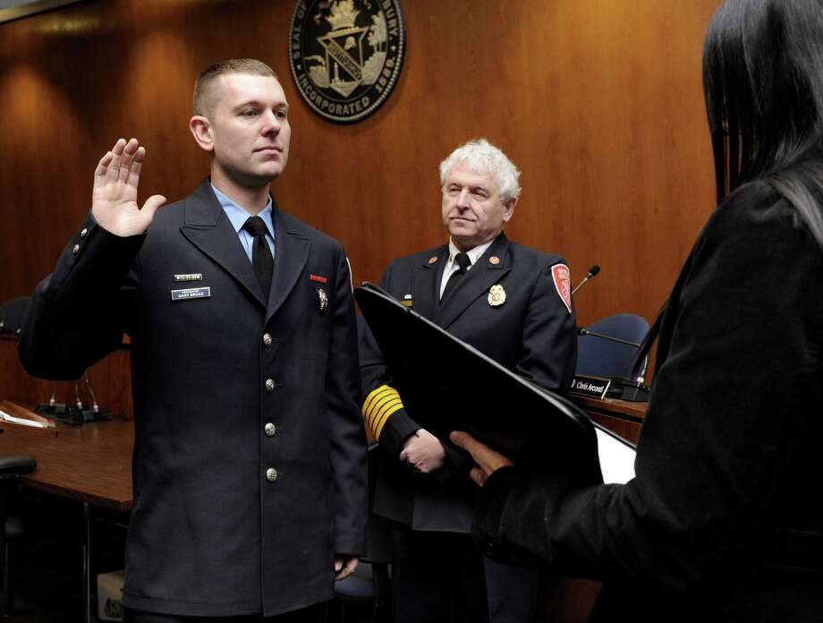 Gary Bruce, 34, left, is sworn in as Deputy Fire Marshal by Town Clerk Lori Kaback at a promotion at Danbury City Hall Wednesday, March 5, 2014, in Danbury, Conn.  Fire Chief Geoff Herald is center. Photo: Carol Kaliff / The News-Times