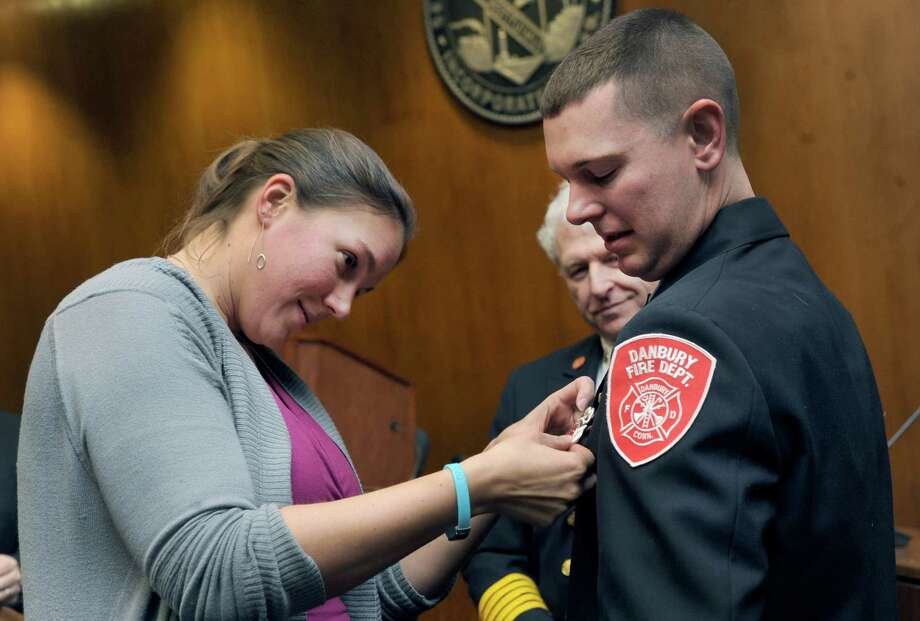 Rebecca Bruce, 32, pins on her husband's new badge after he is sworn in as deputy fire marshal at City Hall in Danbury, Conn., Wednesday, March 5, 2014. Photo: Carol Kaliff / The News-Times