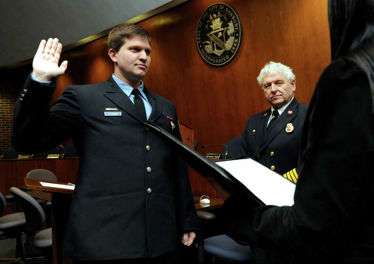 Shey Hanson, 35, left, is sworn in as a lieutenant in the Danbury Fire Department by Town Clerk Lori Kaback at a promotion at Danbury City Hall Wednesday, March 5, 2014, in Danbury, Conn. Fire Chief Geoff Herald is center.