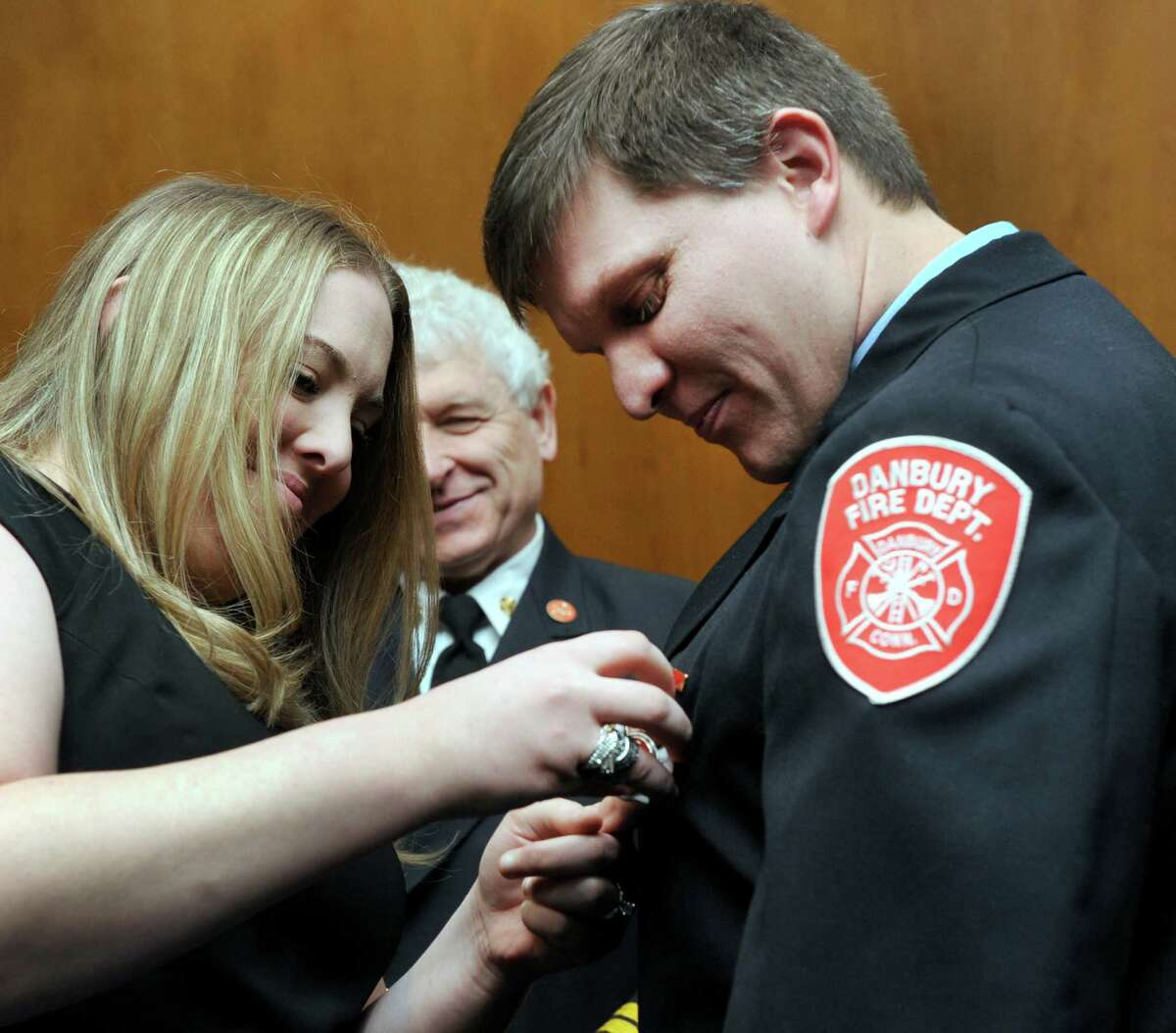 Jessica Hanson, 29, pins a badge on her husband Shey Hanson, 35, who has just been promoted to the rank of lieutenant in the Danbury Fire Department Wednesday, March 5, 2014, at ceremony at Danbury City Hall.