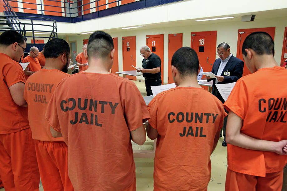 Daniel Lozano (center) and Juan Torres read a prayer as inmates at the Bexar County Jail come forward to receive the imposition of ashes on March 5, 2014. Photo: TOM REEL