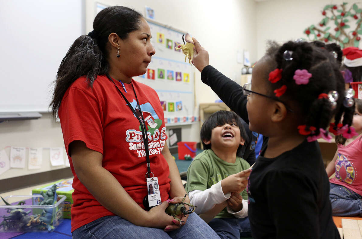 Pre-K teacher assistant Krystal Garcia pauses with Mya Johnson, 4 (right), and Victor Victela, 5, at the South Pre-K 4 SA Center in San Antonio. Officials hope the program will better prepare students for higher grades and beyond.