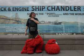 50-year-old Dan Sandler takes a break from posing for photos with tourists dressed as Elmo in Fisherman's Wharf on March 5th 2014. Sandlers has been known to go on various heated controversial rants while wearing the costume.