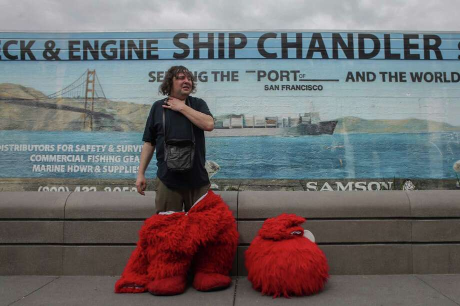 Dan Sandler takes a break from posing for photos with tourist dressed as Elmo in Fisherman's Wharf on March 5th 2014. Sandlers has been known to go on various heated controversial rants while wearing the costume. Photo: Sam Wolson / Special To The Chronicle / ONLINE_YES