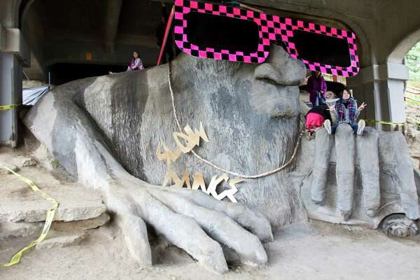 """The famed Fremont Troll sports a new look with giant sunglasses and a gold chain necklace saying, """"slow dance,"""" right after the 23rd Annual Fremont Solstice Parade Saturday, June 18th, 2011"""