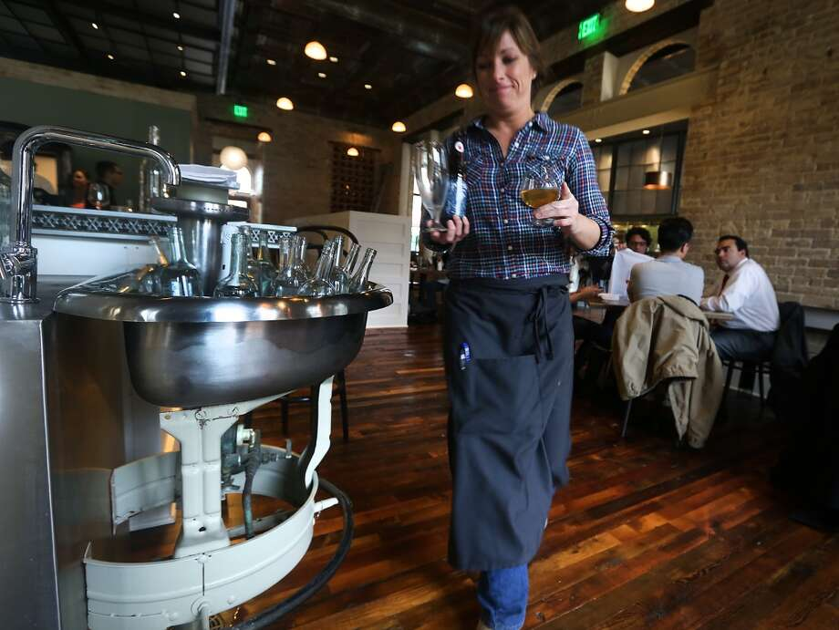 Elizabeth Speer, a server at Cured in The Pearl, walks past what was a hand washing station from a men's room at the old Pearl Brewery that is now used as a water bottle chiller at the restaurant. Photo: BOB OWEN, San Antonio Express-News