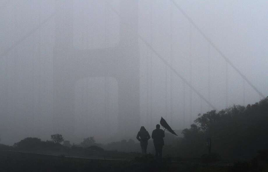A gust of wind gets the better of an umbrella carried by a visitor to Battery Spencer, overlooking the Golden Gate Bridge, in Sausalito, Calif. on Saturday, Feb. 8,  2014. (AP Photo/ Marin Independent Journal, Alan Dep) Photo: Alan Dep, Associated Press