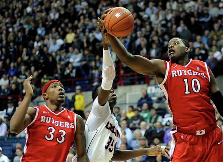 Connecticut's Amida Brimah,  center, reaches for a rebound with Rutgers' Wally Judge (33) and Junior  Etou (10) during the first half of an NCAA college basketball game in  Storrs, Conn., Wednesday, March 5, 2014. (AP Photo/Fred Beckham)