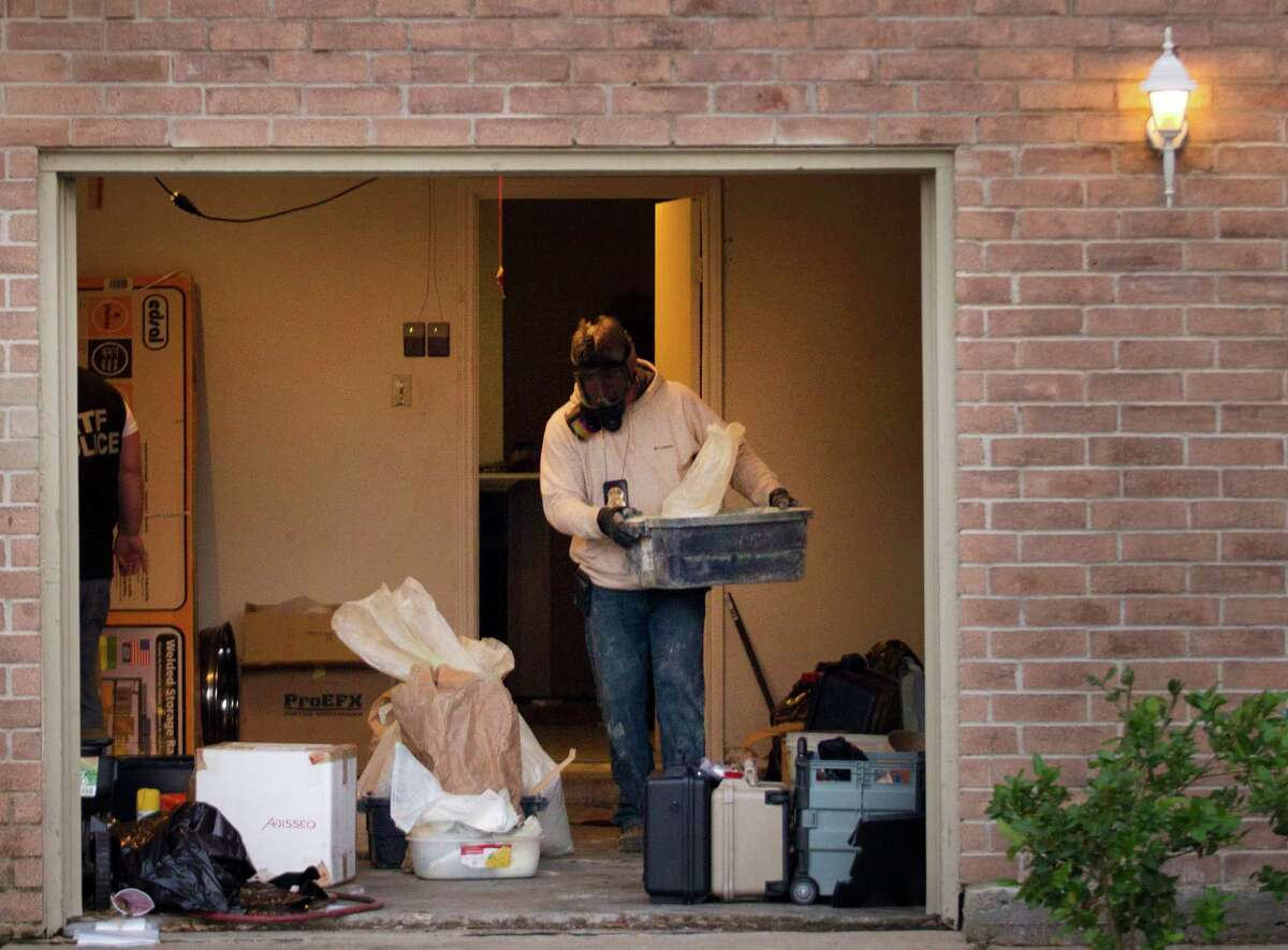 Federal law enforcement officers investigate the scene of an alleged pill mill in the 17600 block of Patti Glen on Wednesday,