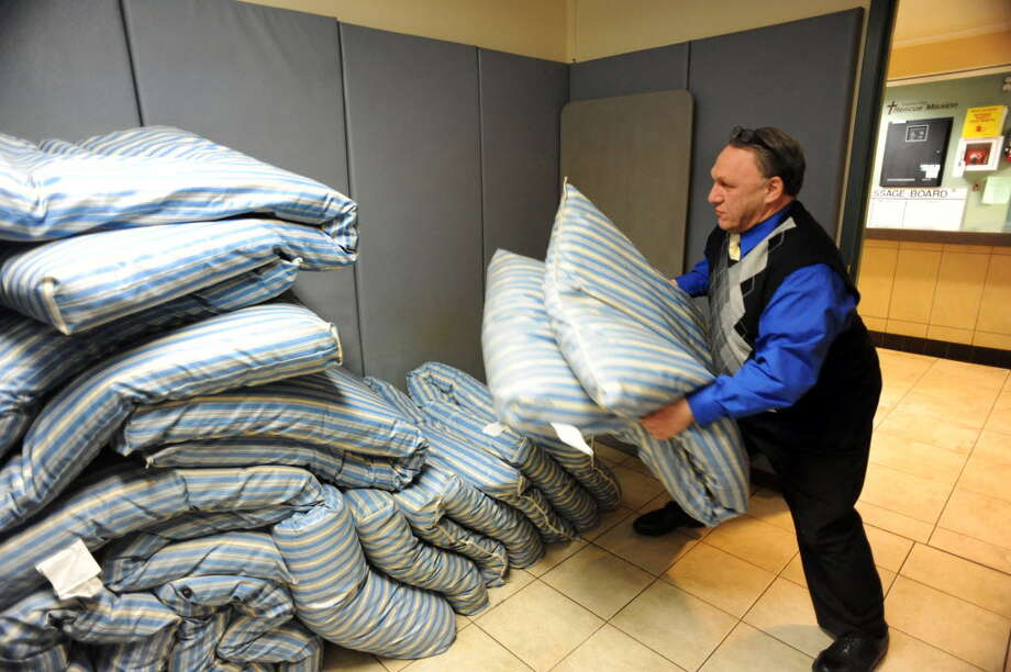 Perry Jones, executive director of Capital City Rescue Mission on South Pearl Street, moves mattresses for Code Blue clients on a cold night in January. (Times Union archive)
