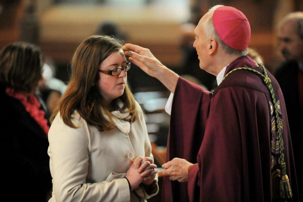 Bishop Howard Hubbard, right, places ashes on the forehead of parishioner Erin Knoerl of Albany on Wednesday, March 5, 2014, at the Cathedral of the Immaculate Conception in Albany, N.Y. Hubbard presided over his last Ash Wednesday as bishop. (Cindy Schultz / Times Union)