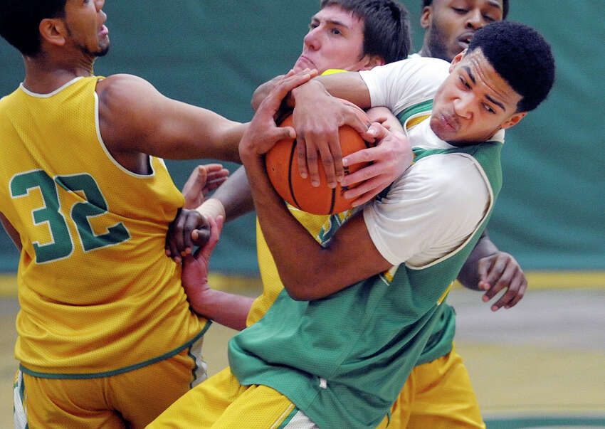 Siena men's basketball player Michael Wolfe, right, hangs onto the ball as teammates try to strip it out of his hands during a drill at practice on Wednesday, March 5, 2014, in Loudonville, N.Y. (Paul Buckowski / Times Union)