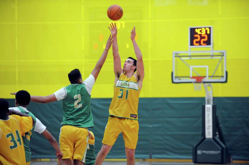 Siena men's basketball player Javion Ogunyemi, left, tries to block the shot of fellow player Brett Bisping during a drill at practice on Wednesday, March 5, 2014, in Loudonville, N.Y. (Paul Buckowski / Times Union)