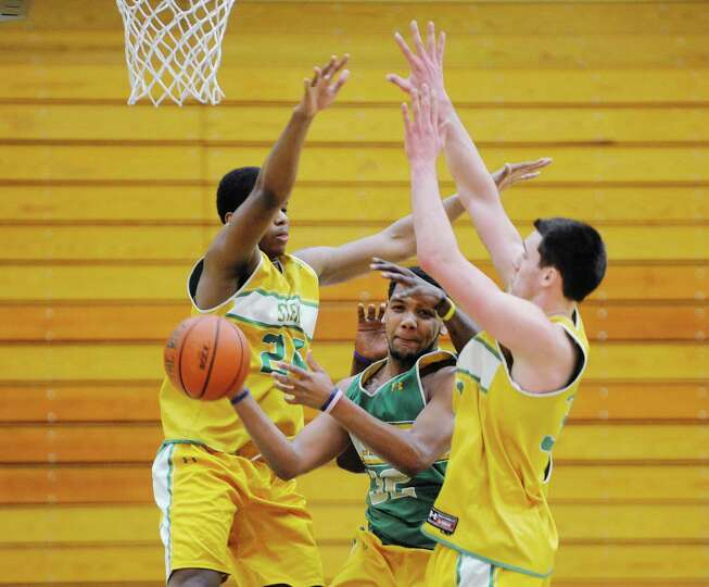 Siena men's basketball player Patrick Cole, center, looks for a teammate to pass to as fellow teamma