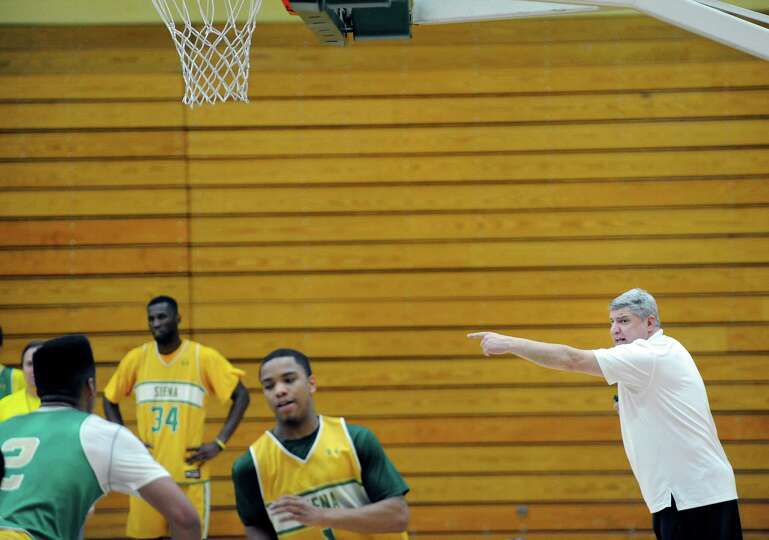 Siena men's basketball head coach Jimmy Patsos, right, yells instructions at players as they run thr