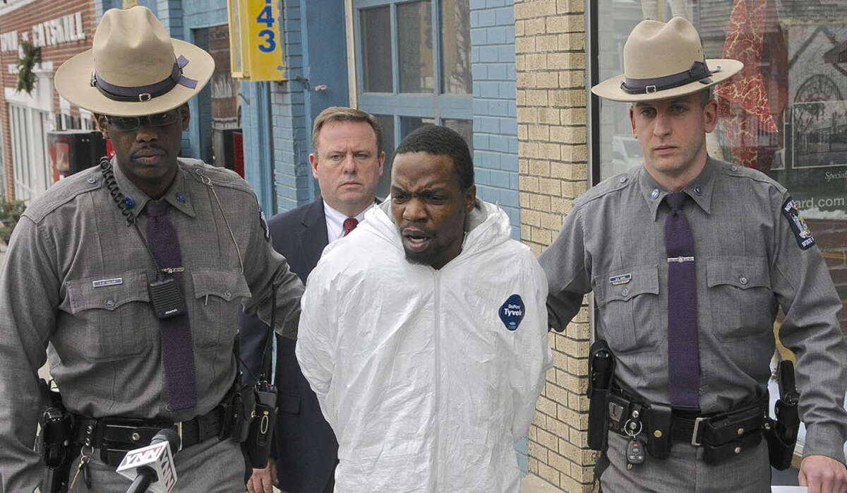 Maurice Pratt, center, in white jumpsuit, is led by State Troopers Amauris Soler, left, and Bernard Davis, as Senior Investigator Scott Youngblood follows in January 2013. (File photo / Special to Times Union by Lance Wheeler)