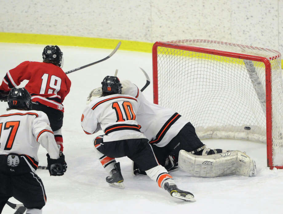 At left, Harry Stanton (#19) of New Canaan scores the winning goal in overtime getting the puck past Ridgefield goalie Patrick Sheehan-Delany as Ridgefield's Shane Luery (#10) defends as New Canaan defeated Ridgefield 3-2 during the FCIAC boys hockey semifinal between Ridgefield High School and New Canaan High School at Terry Conners Rink in Stamford, Conn., Wednesday, March 5, 2014. Photo: Bob Luckey / Greenwich Time