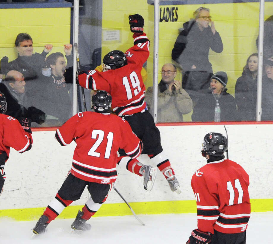 Harry Stanton (#19) of New Canaan jumps in celebration after scoring the winning goal in overtime to defeat Ridgefield 3-2 during the FCIAC boys hockey semifinal between Ridgefield High School and New Canaan High School at Terry Conners Rink in Stamford, Conn., Wednesday, March 5, 2014. Joining in on the celebration are New Canaan players, Parker Lewis (#21) and John O'Rourke (#11). Photo: Bob Luckey / Greenwich Time