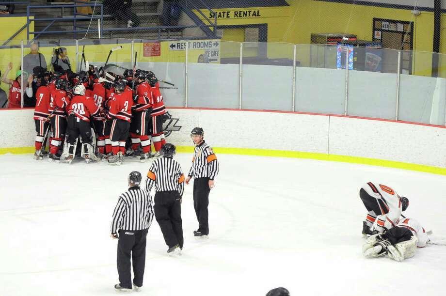 At left, New Canaan mobs teammate Harry Stanton who scored the winning goal in overtime during the FCIAC boys hockey semifinal between Ridgefield High School and New Canaan High School at Terry Conners Rink in Stamford, Conn., Wednesday, March 5, 2014. New Canaan won 3-2 in OT to advance to the final. Photo: Bob Luckey / Greenwich Time